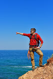 Climber pointing to ocean Royalty Free Stock Images