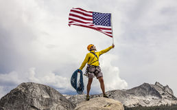 Climber raising the flag on the summit. Royalty Free Stock Photos
