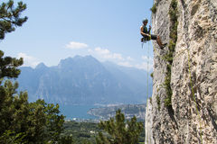 Climber rapelling from rock. A climber is rapelling or abseiling from a limestone rock in Arco. There is lago di Garda and Dolomites mountains in the background Stock Photos