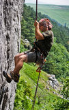 Climber rappeling. Young man in rappel after successfully climbing to the top Royalty Free Stock Images