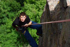 Climber rappelling. A male climber rappelling on a green forest background Royalty Free Stock Photos