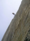 Climber rappelling a cliff face in the Swiss Alps Royalty Free Stock Image