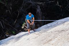 Climber rappelling after climbing a rock wall royalty free stock images