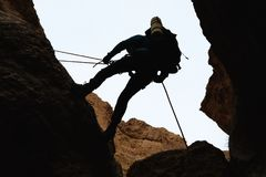 Climber rappelling from a rock. Royalty Free Stock Image