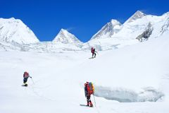 Climber reache the summit of mountain peak. Three climber on the glacier. Success, freedom and happiness, achievement in mountains. Climbing sport concept stock images