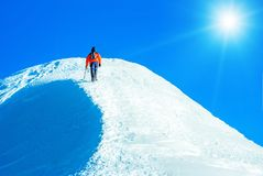 Climber reaches the summit of mountain peak. Climbing and mounta Royalty Free Stock Photography