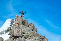 Climber reaches the summit of mountain peak. Success, freedom and happiness, achievement in mountains. Climbing sport concept. royalty free stock photography