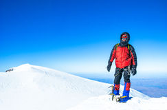 A climber reaching the summit of the mountain. Stock Images