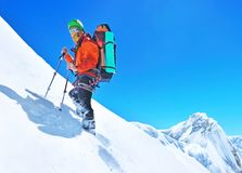 A climber reaching the summit of the mountain. Mountaineer spor Royalty Free Stock Image
