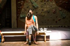 The boy kisses and hugs his mother. The climber rest after a workout. Training in the bouldering hall. The boy kisses and hugs his mother. A women trains with a royalty free stock photos