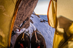 Climber resting in a tent with crampons on their boots Royalty Free Stock Image