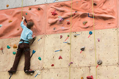 Climber rises to the climbing wall. Stock Photography