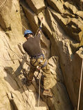 Climber on the rock. Climber hanging on the rock with mountaineering climbering equipment. Extremal sport background Stock Image