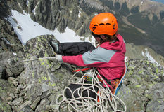 Climber with the rope on mountain summit. Rocky mountain peaks and glacier. Alpinist with equipment - ice axe, crampons and rope. Beautiful scenery, the view Stock Images