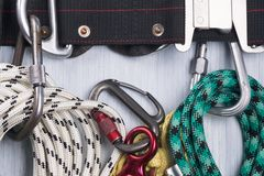 Climber`s belt with different ropes and carbines for insurance lie on a light background, close-up stock photography