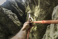 Climber`s hand clicks the rope in carbine. The climber`s hand clicks the rope in carbine. Rock climbing royalty free stock photo