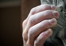 Climber's hand hanging on to artificial hold. Chalked hand grips tightly to hang off an artificial climbing hold. Shallow depth of field Stock Image