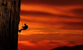 Climber silhouette over beautiful sunset. Man rock climber silhouette over bright sunset Stock Images