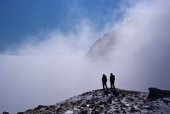 Climber silhouettes in mountains. Two climber silhouettes in mountains covered in fog stock photos