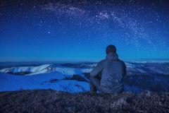 A climber sitting on a ground at night. Milky way in a starry sky above the mountain valley Stock Image