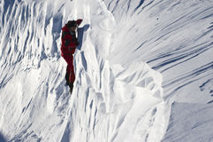 Climber in the snow. Mountaineer climbing a dangerous wall of snow Stock Image
