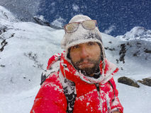 Climber in a snow storm in the mountains, man trekker after trek to Everest Base camp. Active sport in mountains, mountaineer in snowy mountains, red jacket Royalty Free Stock Photos