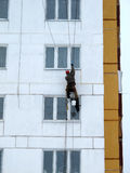 Climber spends repair work on a multi-storey building height Stock Photos