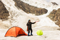 The climber standing near tent on glacier Stock Photo