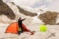 The climber standing near tent on glacier Royalty Free Stock Images