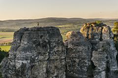 Rock climbing during sunset in a beautiful landscape. Climber standing on the top of a sandstone hill, looking into the landscape Stock Image