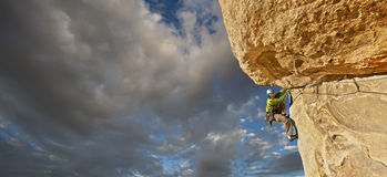 Climber struggles up a cliff. Stock Image