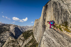 Climber on the summit. Climber peers over the edge of an abyss in Yosemite National Park Royalty Free Stock Image