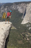 Climber on the summit. Climber peers over the edge of an abyss in Yosemite National Park Stock Images