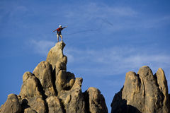 Climber on the summit. Climber on the summit of a rock spire in the Sierra Nevada Mountains, California, on a summer day Stock Image