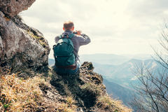 Climber take a mountain landscape photo on his smartphone Stock Photo
