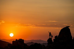 Climber on the top. Male climber celebrates on the summit at sunset Royalty Free Stock Photos