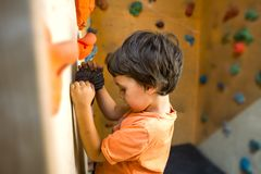 The boy trains on a climbing wall. stock photography