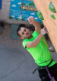 Climber trying to reach a hold on Climbing Wall Stock Photo