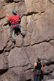 Climber up wall with belayer Stock Photos