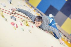 Climber on wall.Young man practicing rock climbing on a rock wal Royalty Free Stock Photography