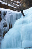 Climber in winter mountains on icefall wall Stock Photos