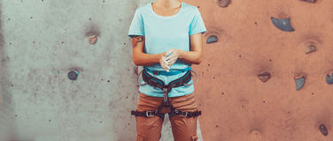 Climber woman coating her hands in magnesia Stock Photos