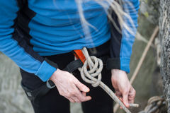 Climber woman in safety harness tying rope in bowline knot. Close-up of climber woman`s hands in safety harness tying rope in double bowline knot and preparing stock images