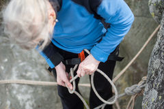 Climber woman in safety harness tying rope in bowline knot. And preparing to climb stock photo
