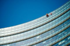 Climber workers for glass cleaning at Porta Garibaldi district, Piazza Gae Aulenti. Royalty Free Stock Image