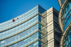 Climber workers for glass cleaning at Porta Garibaldi district, Piazza Gae Aulenti. Royalty Free Stock Photo