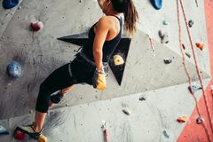Climber young woman climbing on practical wall indoor, bouldering, recreation, sport royalty free stock photography