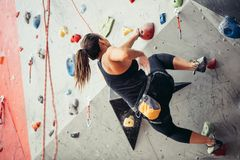 Climber young woman climbing on practical wall indoor, bouldering, recreation, sport royalty free stock images