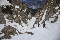 Climbers ascending steep mountain valley in winter stock image