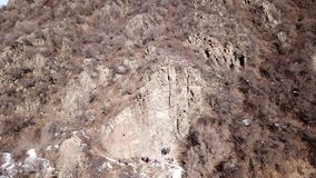 Climbers climb the rock. Drone footage. Side and top view. Rock lesson in the highlands. Gray rocks and dry bushes. Sometimes ther. E is snow. Steep rock and stock photography